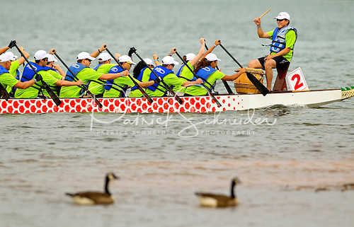 An onboard drummer helps dragon boat competitors paddle in sync along Lake Norman.