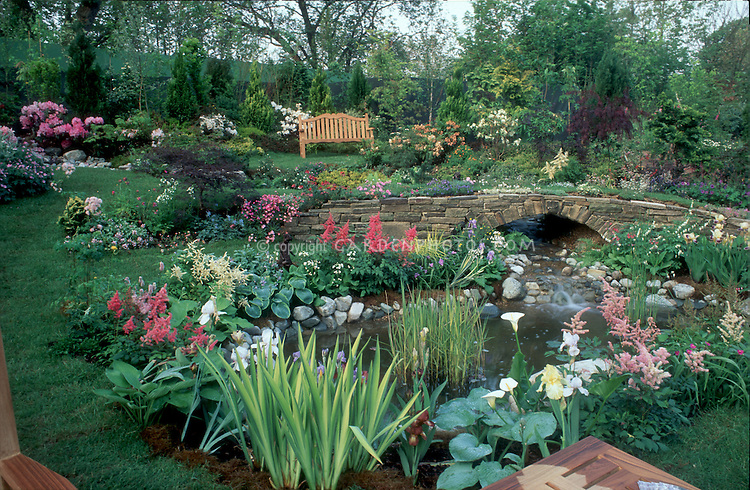 Beautiful garden landscape with bench, water feature, terracing, flowering plants