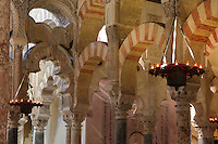 The hypostyle prayer hall, area built in the 10th century under Al-Hakam II, 961-976, in the Cathedral-Great Mosque of Cordoba, in Cordoba, Andalusia, Southern Spain. On the left are fluted intertwined arches with carved decoration. The hall is filled with rows of columns topped with double arches in stripes of red brick and white stone. The first church built here by the Visigoths in the 7th century was split in half by the Moors, becoming half church, half mosque. In 784, the Great Mosque of Cordoba was begun in its place and developed over 200 years, but in 1236 it was converted into a catholic church, with a Renaissance cathedral nave built in the 16th century. The historic centre of Cordoba is listed as a UNESCO World Heritage Site. Picture by Manuel Cohen