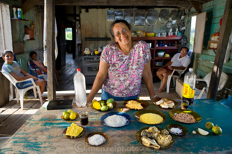 Solange Da Silva Correia, a rancher's wife, with family members in their house overlooking the Solimoes River, with her typical day's worth of food. (From the book What I Eat: Around the World in 80 Diets.)  The caloric value of her day's worth of food on a typical day in the month of November was 3400 kcals.  She is 49 years of age; 5 feet 2.5 inches tall; and 168 pounds.  She and her husband, Francisco (sitting behind her, at right), live outside the village of Caviana with three of their four grandchildren in a house built by his grandfather. They raise cattle to earn income?and sometimes a sheep or two to eat themselves?but generally they rely on their daily catch of fish, and eggs from their chickens, for animal protein. They harvest fruit and Brazil nuts on their property and buy rice, pasta, and cornmeal from a store in Caviana. They also purchase Solange's favorite soft drink made from guarana?a highly caffeinated berry indigenous to the country.  MODEL RELEASED.