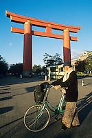 A visitor pauses near the giant torii gate at Heian Jingu shrine in Kyoto.
