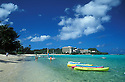 Guam, Micronesia: Tumon Bay resort area with kayaks, beach and Hilton Hotel in distance.