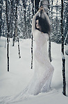 Beautiful woman in white sheer long lace dress leaning against a birch tree in snow covered winter nature scenery