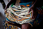 A grandmother holds strings of beads that will be used to adorn a Dipo-Yo (adolescent girl undergoing Dipo). Beads are a form of wealth, handed down from mother to daughter through the generations, and each design has a particular significance. During Dipo, the number of beads worn by a girl is indicative of her family's wealth, as well as the strength of her relationship with them - if she is seen to be respectful older relatives will pitch in and lend her their beads.