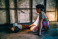 Elita Lugky, 35, sits beside her paralysed daughter Printess, 7, in their house in the North Camp slum. Printess was born prematurely and became paralysed after she contracted polio. Her mother blames American nuclear testing for her polio and all the misfortunes that her family suffered. In 1954, following the Castle Bravo hydrogen bomb test, Elita's parents were evacuated, along with the entire population, from Rongelap Atoll to Ebeye. Many of the Rongelap Atoll inhabitants developed leukaemia and tumours of the thyroid gland after being exposed radioactive fallout from the test. They were allowed back to the atoll three years later but after years of illness enviromental group Greenpeace moved them to Mejato and Ebeye islands. However, Ebeye has become overpopulated and is informally known as the 'slum of the Pacific'. It people suffer numerous diseases and the mortality rate is one of the highest in the Republic of the Marshall Islands.