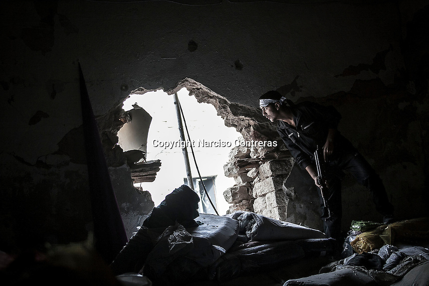 In this Wednesday, Oct. 24, 2012 photo. An FSA soldier watchs over the enemy position as rebel fighters belonging to the Liwa Al Tawhid carry out a militar operation at the Moaskar front line, one of the battlefields in Karmal Jabl neighborhood, northeast of Aleppo City. (AP Photo/Narciso Contreras).