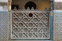 Detail of carved wooden screen around central courtyard, Sahrij Medersa, (Medersa des Andalous), 1321, Fez, Medersa Sahrij, Fez, Morocco, pictured on February 23, 2009 in the morning.  The Sahrij Medersa takes its name from the pool in its courtyard, (sahrij means basin). Green and white minarets crown the theological school founded by Merinid sultan Abou al-Hassan and attached to the Al-Andalous mosque.  It is decorated with ornate  dark cedar panels (mashrabiya), decorated tiles (zellij), marble pavings and intricate plasterwork. Fez, Morocco's second largest city, and one of the four imperial cities, was founded in 789 by Idris I on the banks of the River Fez. The oldest university in the world is here and the city is still the Moroccan cultural and spiritual centre. Fez has three sectors: the oldest part, the walled city of Fes-el-Bali, houses Morocco's largest medina and is a UNESCO World Heritage Site;  Fes-el-Jedid was founded in 1244 as a new capital by the Merenid dynasty, and contains the Mellah, or Jewish quarter; Ville Nouvelle was built by the French who took over most of Morocco in 1912 and transferred the capital to Rabat. Picture by Manuel Cohen.