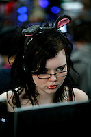 Girl with bunny ears. One of the world's largest convention of computer enthusiasts, simply called 'The Gathering'. Over five thousand young people come together each Easter, some travelling long distances, each carrying their own computer equipment to the massive Vikingship sports hall in the city of Hamar. The main activity is online gaming. Many hardly see daylight or taste fresh air for the entire five days as they compete with their fellow geeks for cash prizes and the honour of being the best.