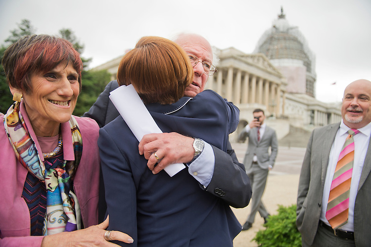 UNITED STATES - JUNE 03: Sen. Bernie Sanders, I-Vt., hugs Rep. Nydia Velazquez, D-N.Y., as Reps. Rosa DeLauro, D-Conn., and Mark Pocan, D-Wisc., look on, during a news conference with other House democrats at the House triangle to urge Congress to not fast-track the Trans-Pacific Partnership and recognize a petition signed by 2 million Americans also opposing it, June 3, 2015. (Photo By Tom Williams/CQ Roll Call)