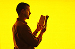 Book reader with yellow background. Photography by Brent McGilvary