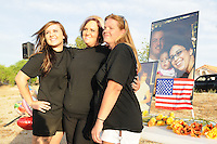 """Gilbert, Arizona – Friends and family of the Mederos Family gathered to hold a memorial for the four victims of the Gilbert Massacre occurred on May 2, 2012. According to Gilbert Police, Lisa Mederos, Amber Mederos, baby Lilly Mederos, and Jim Hiott (Amber's fiancé) were all killed by notorious white supremacist and Neo-Nazi Jason """"J.T."""" Ready before taking his own life. In this image, Whitney Byrd, Crystal Seibert and Mistie Whiteman are photographed by a friend next to a memorial table with flowers and photos of the four victims killed. Photo by Eduardo Barraza © 2012"""