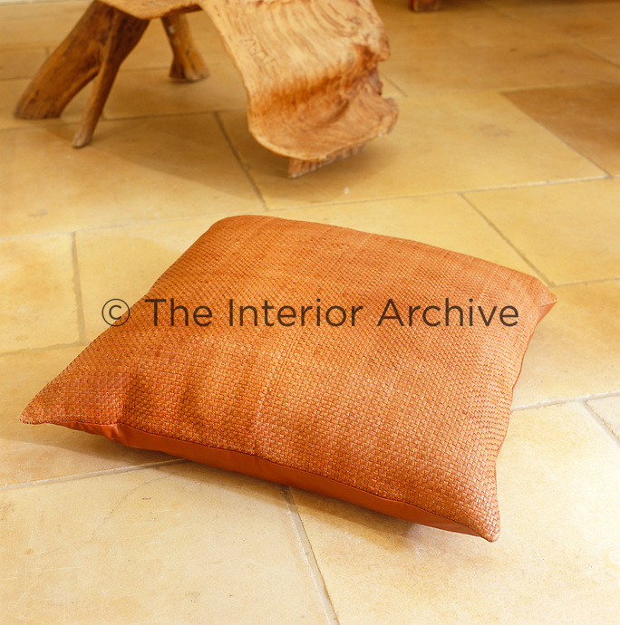 An orange textured cushion seen against the terracotta tiles of a living room floor