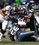 Denver Broncos running back Montee Ball (28) is stopped by Seattle Seahawks  linebacker Bobby Wagner (54) and defensive end Cliff Avril (56) at CenturyLink Field in Seattle, Washington on September 21, 2014. The Seahawks won 26-20 in overtime.    ©2014. Jim Bryant Photo. All rights Reserved.