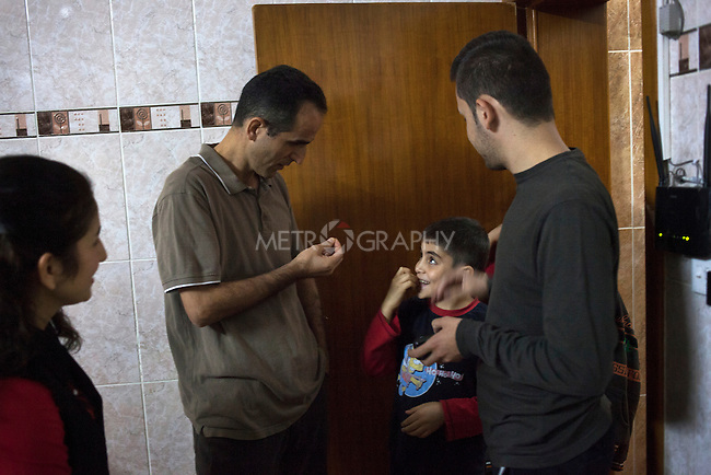 "21/10/14. Erbil, Iraq. Milad and Wassam's uncle Salam (left) prepares to take the brothers out for a walk to buy snacks. Milad (centre) is impatient, Salam says, ""My son, I said we are going in a minute, slow down!"""