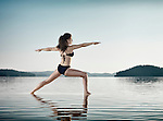 Young woman practicing Hatha yoga on a floating platform in water on the lake during sunrise in the morning over blue sky background. Yoga Warior posture, Dandayamana Dhanurasana. Muskoka, Ontario, Canada.