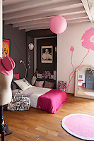 A cheerful pink and white mural covers one wall of this girl's bedroom offset by the dark grey wall opposite