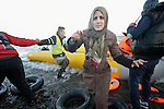 A refugee woman arrives on a beach near Molyvos, on the Greek island of Lesbos, on November 2, 2015. She and her family were received by local and international volunteers, then proceeded on their way toward western Europe. The boat was provided by Turkish traffickers to whom the refugees paid huge sums to arrive in Greece.