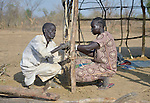 Aluel Yuot (right) and her husband James Biar tie sticks together as they construct a shelter in the internally displaced persons camp in Turalei, South Sudan. Families started arriving here shortly after fighting broke out in December 2013, and new families continued to arrive in March 2014 as fighting continued. Many are living in the open and under trees. The ACT Alliance is providing the displaced families and the host communities affected by their presence with a variety of support, including new wells.