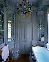 A bathroom with mirrored walls and grand chandelier