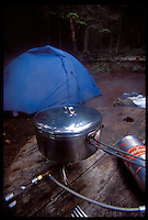 A STAINLESS STEEL COOKPOT SIMMERS ON A STOVE WHILE A TENT IS SEEN IN THE BACKGROUND ON ISLE ROYALE NATIONAL PARK.