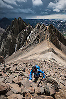 Female hiker ascending the rocky southeast couloir of Lavender Col route on Mt. Sneffels (14150 ft), San Juan mountains, Colorado, USA