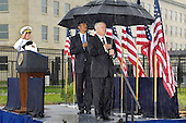 Washington, DC - September 11, 2009 -- Honoring the dead from the September 11, 2001, terrorist attack on the Pentagon, United States President Barack Obama (center) joined U.S. Secretary of Defense Robert M. Gates (right) and Chairman of the Joint Chiefs of Staff Navy Admiral Mike Mullen (left), under rainy skies, for a wreath laying ceremony at the Pentagon Memorial.  Here the officials salute at the playing of the national anthem.  Attendance at the 8th anniversary ceremony was limited to those individuals or families who actually lost a loved-one in the attack.  .Mandatory Credit: Robert D. Ward - DoD via CNP