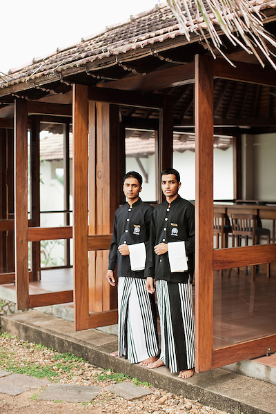 Two waiters stand at the doorway of the Pool Bar ready to welcome guests at Saman Villas, Aturuwella, Bentota, Sri Lanka.