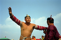 "Zuunmod, Mongolia, July 2003..Competitors and spectators at the Mongolian Wrestling contests in the Llama Naadam. A wrestler ""flies like a falcon"" around a judge."