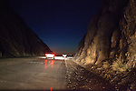 Cars driving on the Pacific Coast Highway through rocky mountains at night in Malibu, California, USA