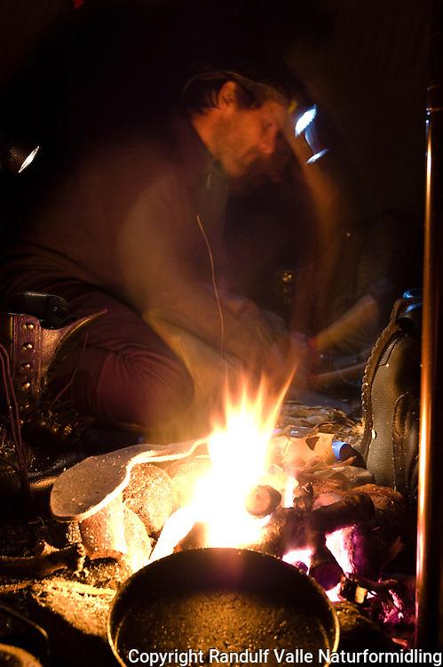 Mann hugger ved i lavvo --- Man chopping wood inside tent