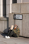 homeless man sits beneath london bridge sign