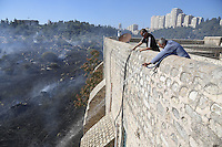 A monk from the monastery of the cross, in the valley of the cross, in Jerusalem, helps extinguish forest fire which broke out in the valley earlier today, July 02, 2013.  Photo by Oren Nahshon