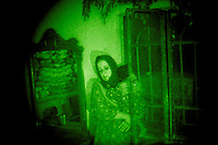 ISKANDARIYA, IRAQ - JULY 15: A terrified Iraqi woman holds a sleeping child as US soldiers record her biometrics and interogate her during a raid on July 15, 2007 in Iskandariya, Iraq. The raid targeted IED production and a search for suspected insurgets. The area south of Baghdad has had little US army presence in the last 6 months, and is considered a haven for Al Qaeda in Iraq. (Photo by Benjamin Lowy/Reportage by Getty Images)