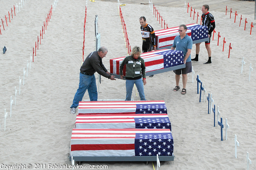 Veterans for Peace volunteers carry flag draped coffins at Arlington West for the Veterans Day memorial on Friday, November 11, 2011.