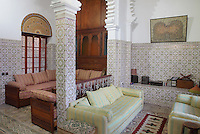Seating area adjacent to the ground floor central courtyard, with zellige tile decoration on the walls, in a typical Tetouan riad, a traditional muslim house built around a courtyard, built in Moorish style with strong Andalusian influences, next to the Great Mosque or Jamaa el Kebir in the Medina or old town of Tetouan, on the slopes of Jbel Dersa in the Rif mountains of Northern Morocco. Tetouan was of particular importance in the Islamic period from the 8th century, when it served as the main point of contact between Morocco and Andalusia. After the Reconquest, the town was rebuilt by Andalusian refugees who had been expelled by the Spanish. The medina of Tetouan dates to the 16th century and was declared a UNESCO World Heritage Site in 1997. Picture by Manuel Cohen