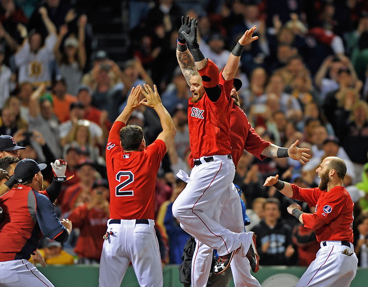 Red Sox outfielder Jonny Gomes is congratulated by Boston teammates after hitting a walk-off homer against the Tampa Bay Rays at Fenway Park on Tuesday, June 18, 2013