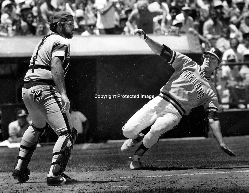 A's Bruce Bochte slides in to home. (1984 photo by Ron Riesterer)