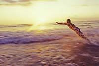 Man diving into surf at sunset, Polihale, Kauai, Hawaii