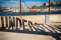 """Projected shadow of the rotating """"Understanding"""" public art sculpture in Brooklyn Bridge Park in New York on Sunday, October 23, 2016. """"Understanding"""" by the artist Martin Creed features a 25 foot tall rotating red sculpture spelling out the word understanding reminiscent of a billboard on the side of a highway.  (© Richard B. Levine)"""
