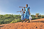 Two girls walk to school along a rural road near Kanyemba, in northern Malawi. They carry hoes so they can work in their family farm fields after class.