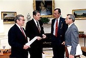 United States President Ronald Reagan meets with senior staff in the Oval Office of the White House in Washington, D.C. on Sunday, April 12, 1987 for a National Security Briefing.  Shown, from left, are: White House Chief of Staff Howard Baker; President Ragan; U.S. Vice President George H.W. Bush; and National Security Advisor Frank Carlucci..Mandatory Credit: Bill Fitz-Patrick - White House via CNP
