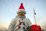 Garden City, New York, USA. December 1, 2013. The NASA astronaut statue, wearing a Santa hat and holding a Christmas wreath for the holidays, is at the entrance to tthe Cradle of Aviation Museum grounds during the Winter holiday Festival of Trees held at the museum during Thanksgiving weekend. Event proceeds benefited United Cerebral Palsy Association of Nassau County, Long Island.