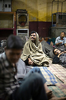 Men watch television in the Fatepuri night shelter for the homeless in Old Delhi.
