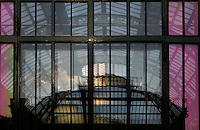 New Caledonia Glasshouse (formerly The Mexican Hothouse), 1830s, Charles Rohault de Fleury, Jardin des Plantes, Museum National d'Histoire Naturelle, Paris, France. Detail of folding glass panels reflecting the late afternoon light and the Plant History Glasshouse (formerly the Australian Glasshouse). The New Caledonia Glasshouse, or Hothouse, was the first French glass and iron building.