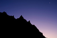 Before daybreak, the sky is purple-blue, a tiny crescent moon cradling the last corner of the night above the jagged shoulder of the mountain. Akadake, Nagano, Japan. <br />