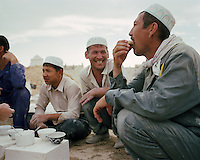 Grave buiders stop for a tea break at the Koshkar-Ata Cemetery on the Caspian Sea coast. These grave builders work from dawn until dusk, sleeping on site for months at a time. .