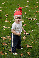Caucasian Kid Girl in Red Hat Standing on Grass