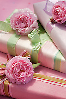 Three presents wrapped in pink paper with contrasting ribbons are topped with roses for a charming finishing touch