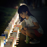 A girl inspects candles lining a path in Nagasaki, Japan, on August 8, 2015, the eve of the 70th anniversary of the U.S. bombing of the port city with an atomic bomb. The candles represent a memorial to those who died and a prayer for peace, including an end to nuclear weapons.