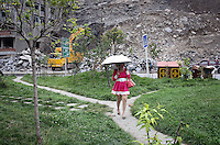 A woman walks through a park in the town of Heishui on the south-east edge of the Tibetan Plateau in Sichuan Province, western China.